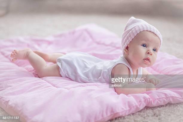Linda niña bebé caer en su estómago mirando curioso
