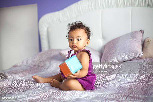 Cute baby girl playing with cube toy on bed