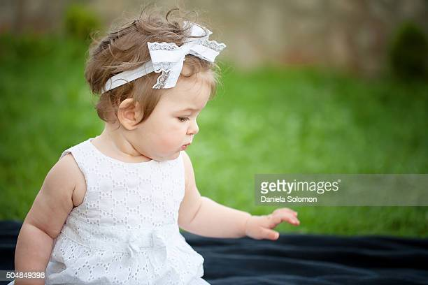Cute baby girl sitting on grass looking away