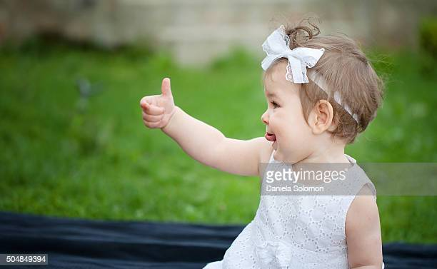 Cute baby girl sitting on grass showing thumb up