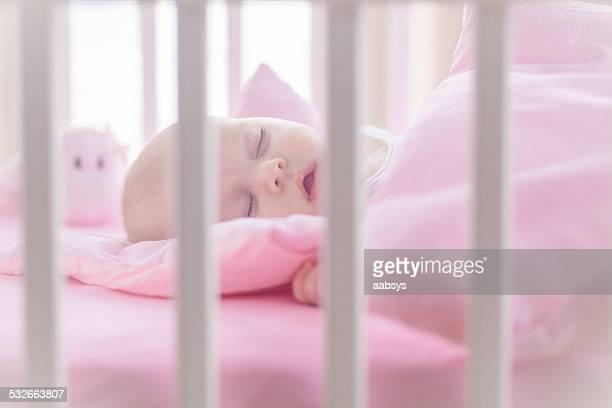 Cute baby girl sleeping in white crib