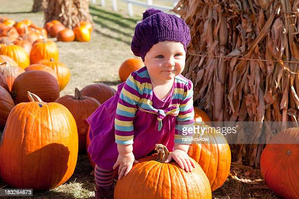A cute baby girl standing with a pumpkin in a pumpkin patch