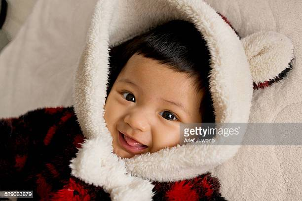 Cute baby girl wearing fluffy snow suit