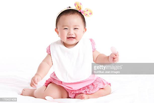 Cute baby girl with bib and spoon