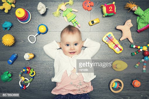 cute baby girl with lot of toys on the floor. top view : Stock Photo