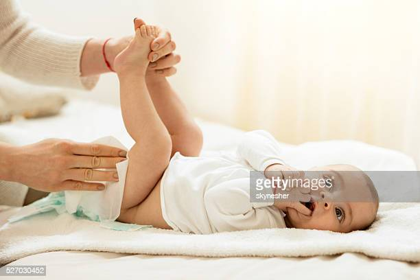 Cute baby in bedroom getting diaper changed.