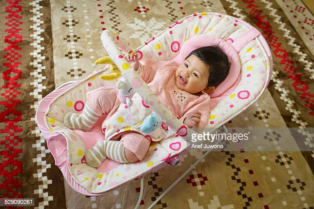 Cute baby playing and sitting in baby bouncer