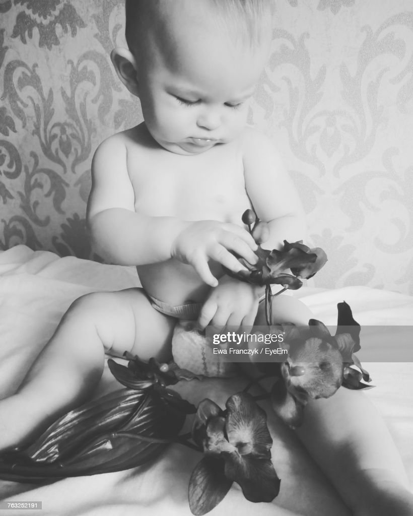 cute baby playing with artificial flowers while sitting on bed at