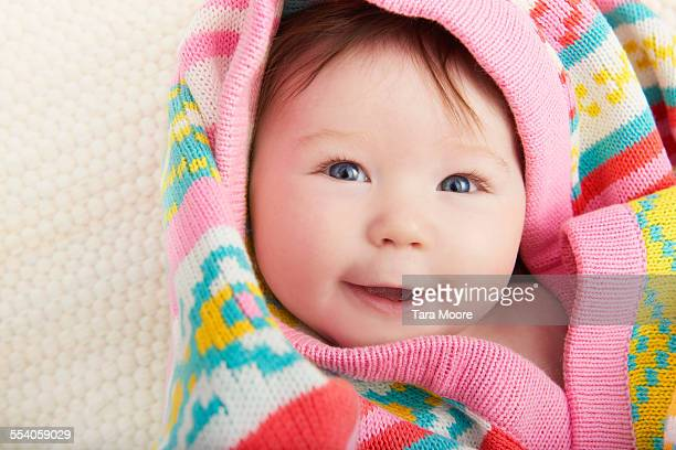 cute baby smiling wrapped in colourful blanket