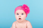 portrait of cute baby with pink bow flower on her head. surprised baby child looking into the camera. lovely kid with big blue eyes. happy family concept