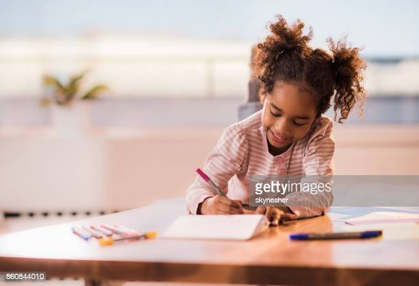 Cute black girl relaxing at home and drawing on a paper.