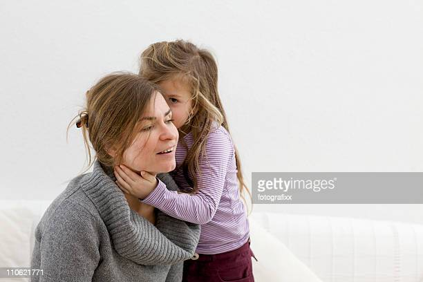 cute blond girl whispers in the ears from mother