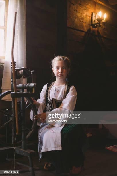 Niedliche blonde kleine Kind Mädchen tragen Tracht aus Holz Spinnrad in alten Haus zu sitzen