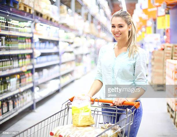 Cute blond woman shopping in supermarket.