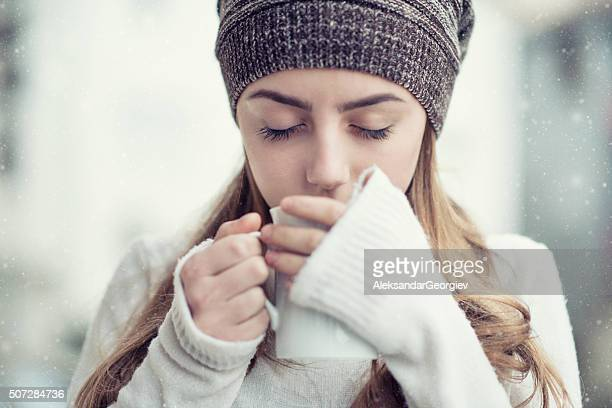 Cute Blonde Girl Drinking hot Tea During the Winter Snow
