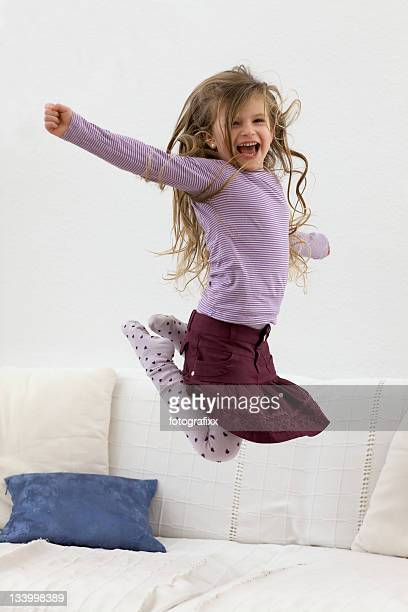 cute blonde girl jumps high on the sofa