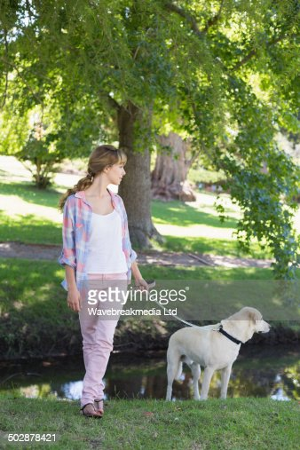 Cute blonde with her labrador dog in the park : Stock-Foto