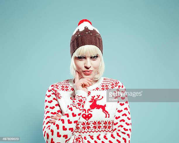Cute blonde young woman wearing xmas sweater and bobble hat