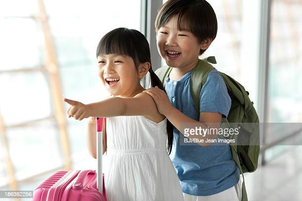 Cute boy and girl looking at view at the airport