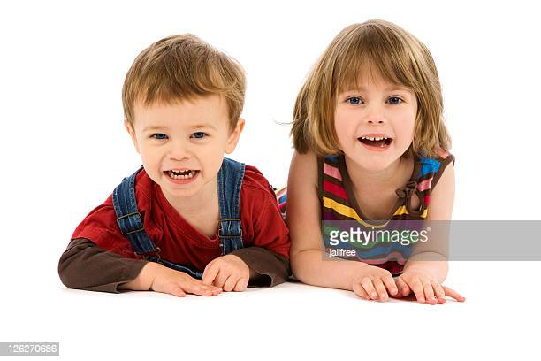 Cute boy and girl lying on white background