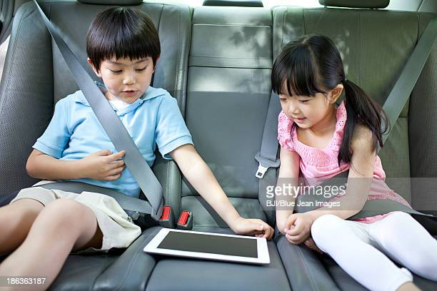 Cute boy and girl playing digital tablet in car