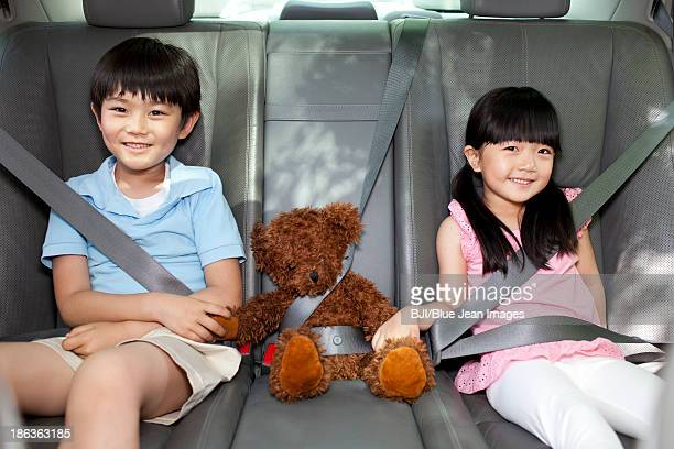 Cute boy and girl with teddy bear sitting in car back seat
