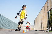 Portrait of preteen boy, happy inline skater, curving around the cones at slalom course in summer
