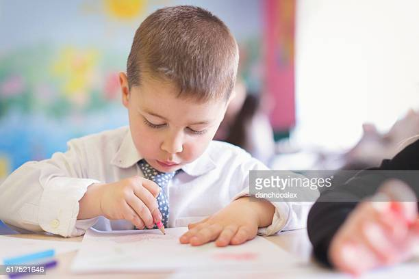 Cute boy drawing in the classroom