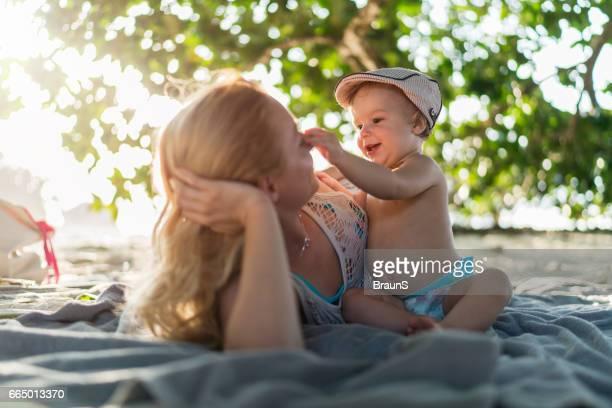 Söt pojke att ha kul med sin mor på stranden.