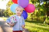 Child going to congratulate a friend on his birthday. Toddler holding bundle of colorful balloons and gift in a festive box. Cute little boy celebrate party with colorful balloons.