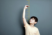 A cute boy is holding his arm up and showing his height on a wall scale.A cute boy is holding his arm up and showing his height on a wall scale.