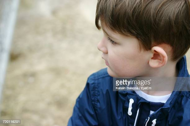 Cute Boy Looking Away While Standing On Field