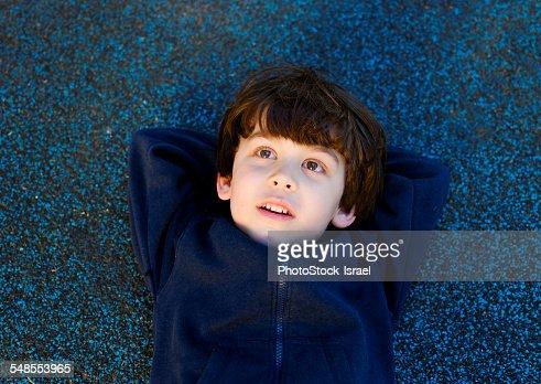 Cute boy lying on back gazing upward
