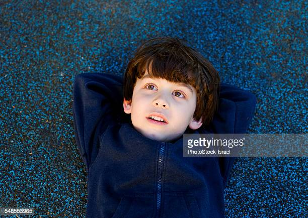 Cute boy lying on back gazing upward