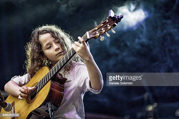 Cute boy playing classical guitar on the stage