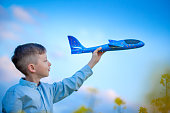 Child plays with a toy airplane in the the blue sky and dreams of travel. Hand with blue toy plane.