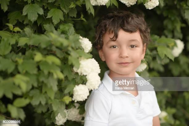 Cute boy posing infront snowball bush