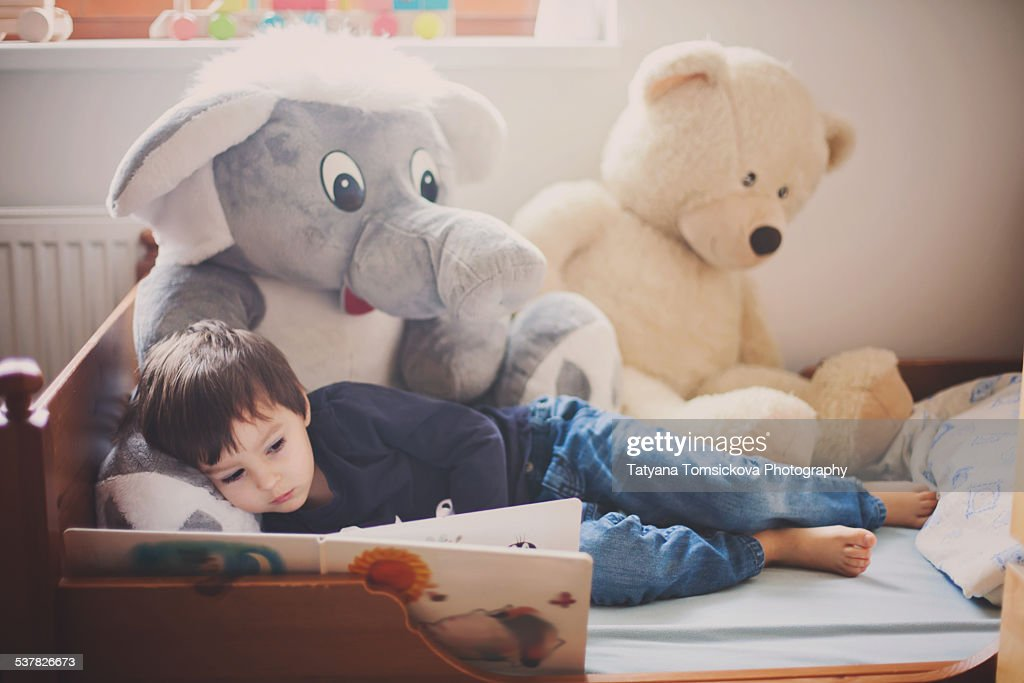 Cute boy, reading a book in bed during the day, teddy bears around him