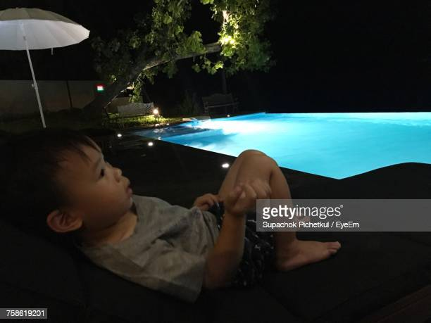 Cute Boy Relaxing On Deck Chair By Swimming Pool