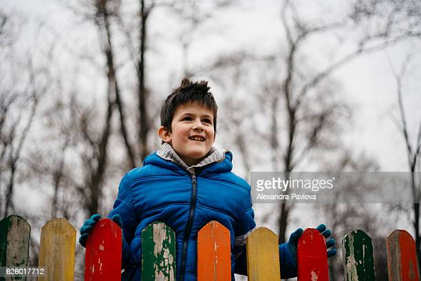 Cute boy smiling, looking over colorful fence