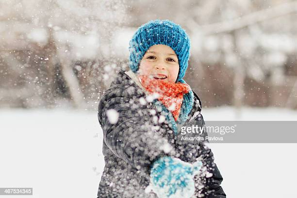 Cute boy throwing a snowball