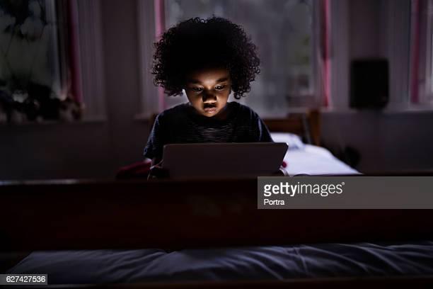Cute boy using digital tablet in dark bedroom
