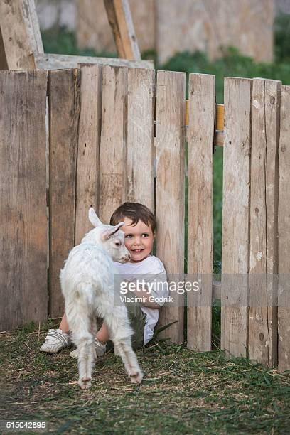 Cute boy with baby goat in park
