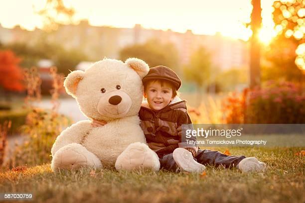 Cute boy with big teddy bear in the park