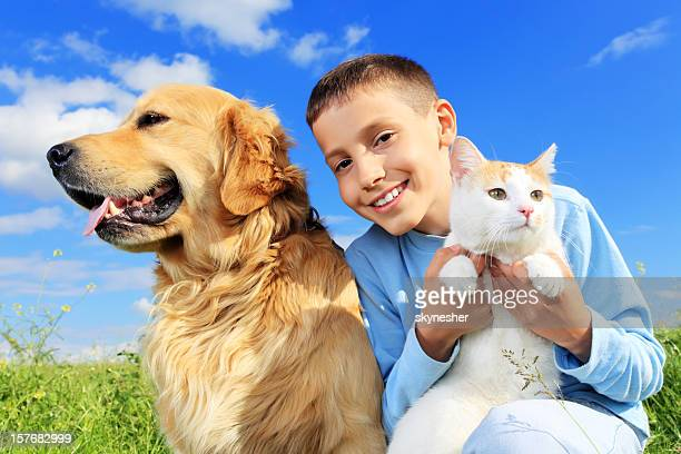 Cute boy with dog and cat outside.
