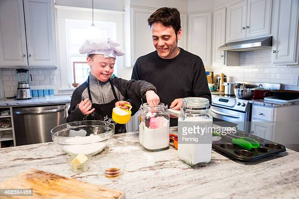 Cute boy with Down Syndrome baking with dad at home