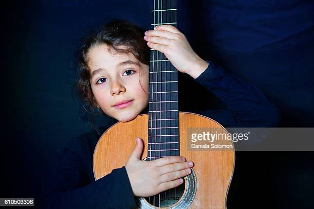 Cute boy with guitar and long hair against blue background