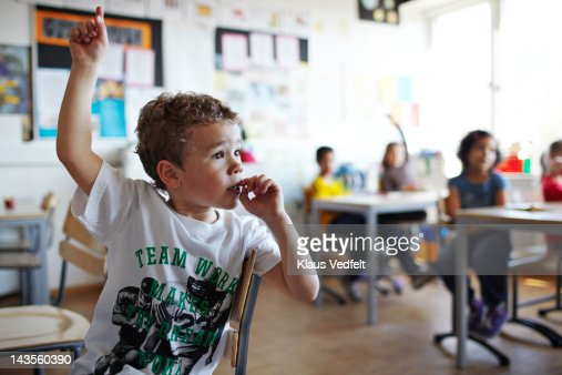 Cute boy with raised hand in classroom
