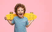 Funny little boy holding yellow skateboard on shoulders and screaming while standing on pink background