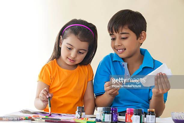 Cute brother and sister painting against colored background